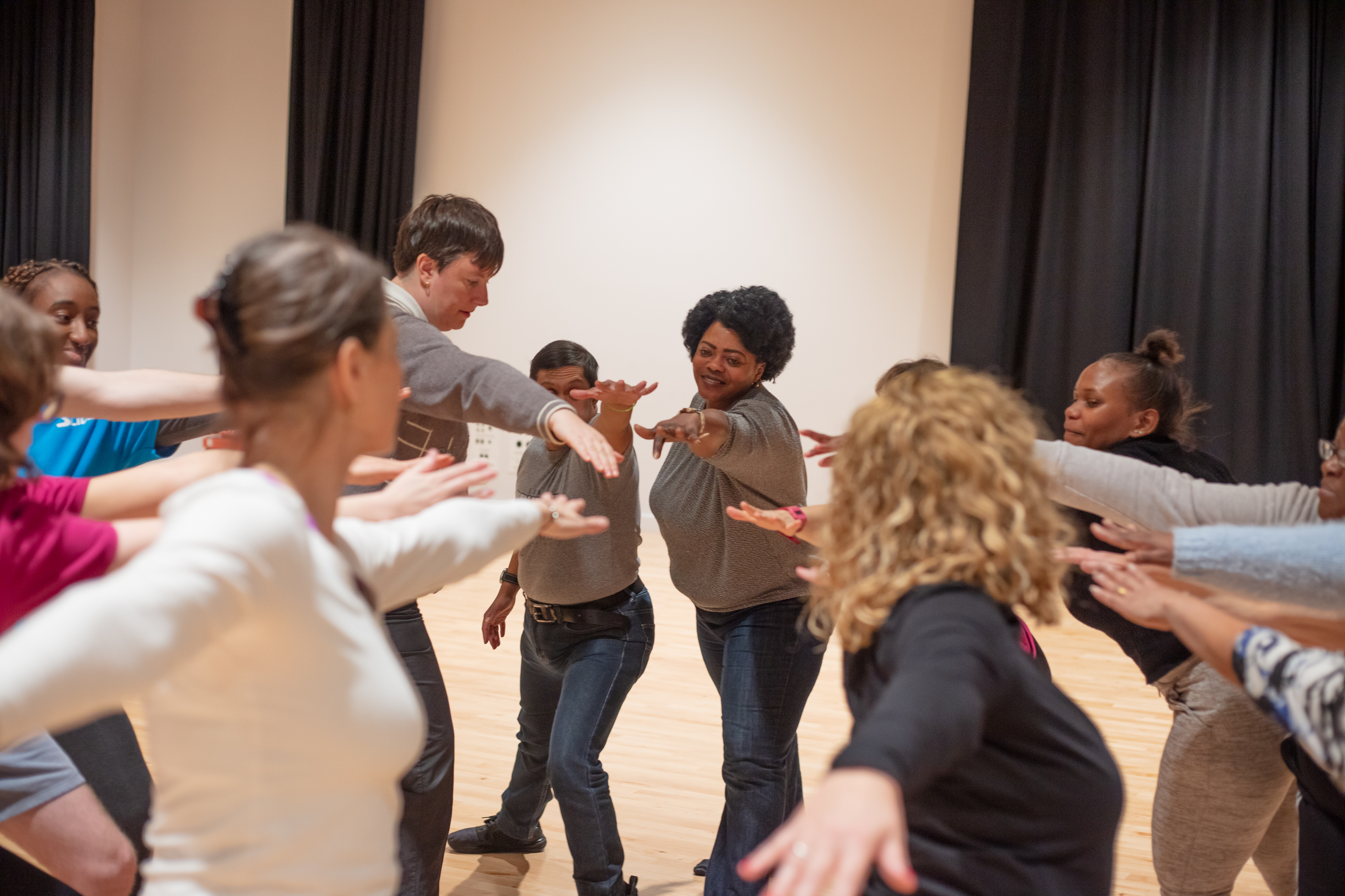 People dancing in a circle with one arm outstretched into the circle centre